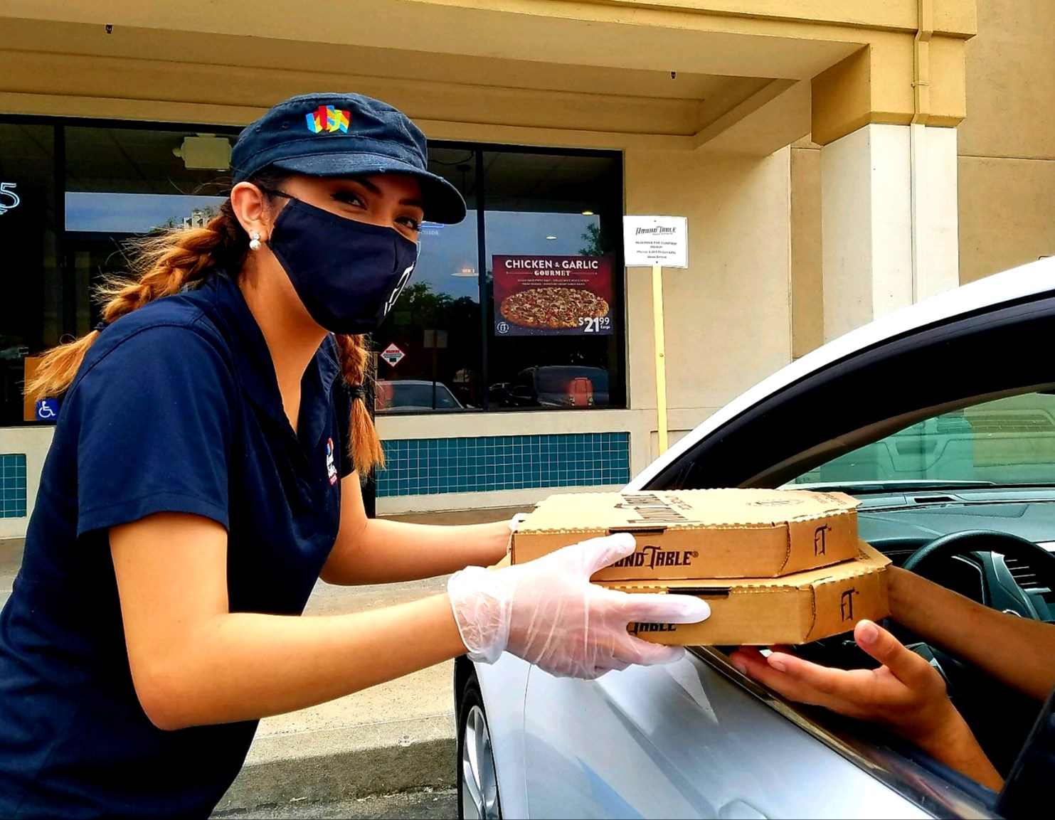 A young lady hand pizza to customers