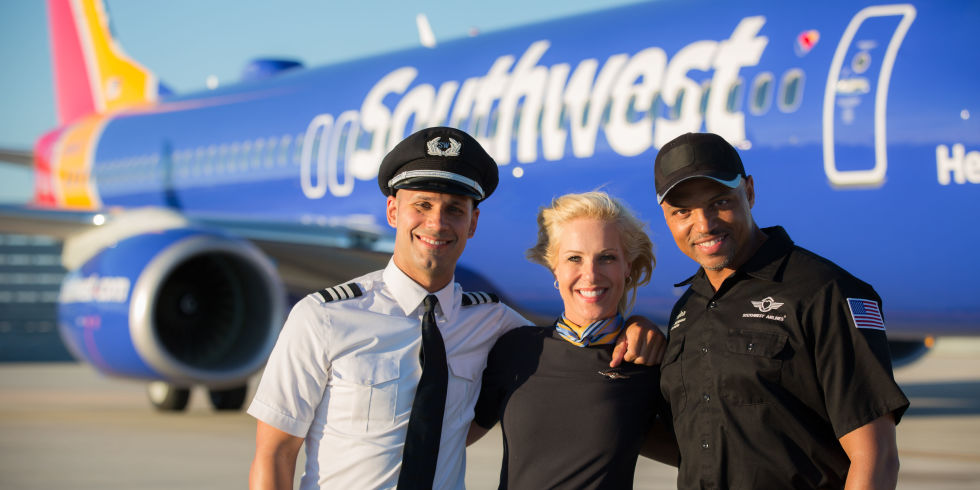 Pilots and fly attendant in front of Southwest aircraft