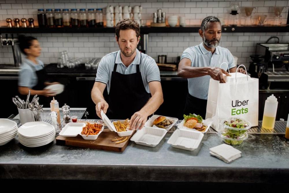 Cloud kitchen staff prepares Uber Eats order