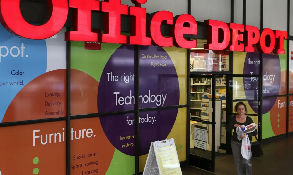 A woman walks out of Office Depot store after shopping
