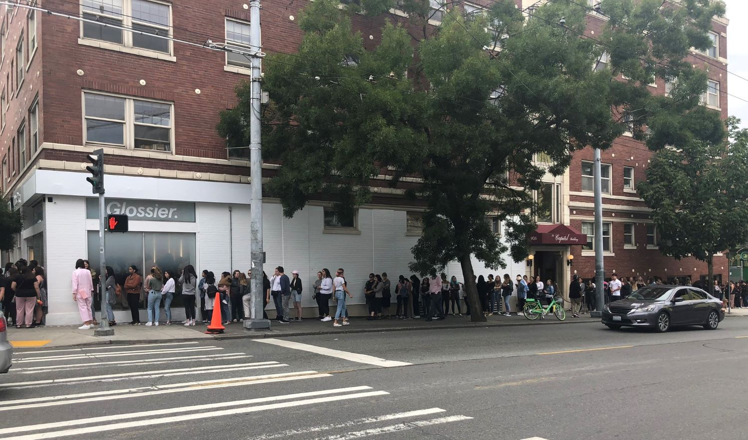 Glossier store with full of people line up