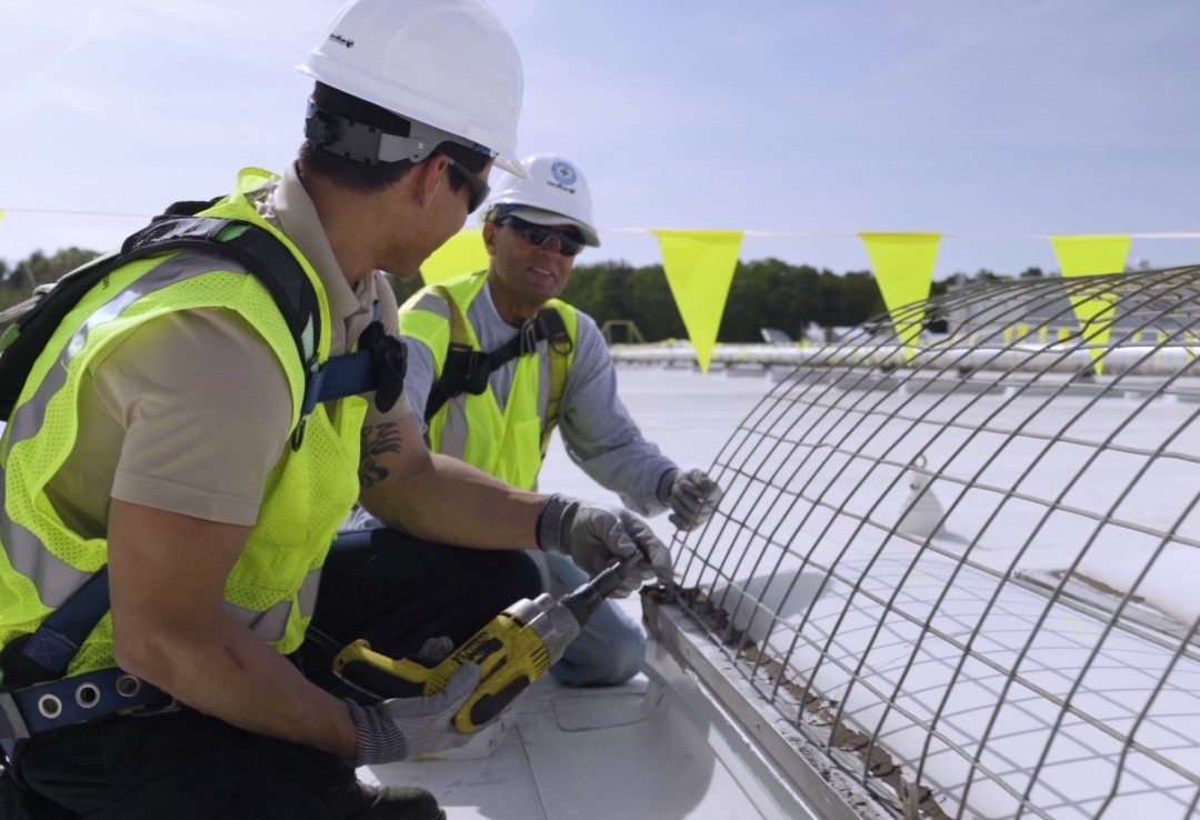 CentiMark staff install device on a roof