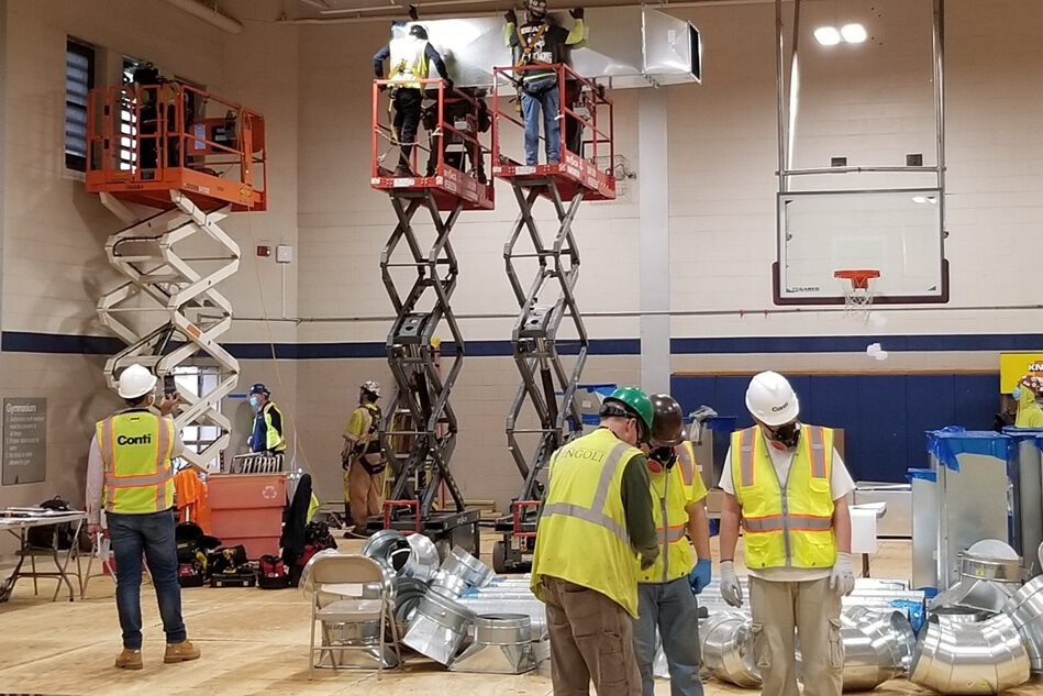 The Conti Group staff assemble HVAC system in basketball court