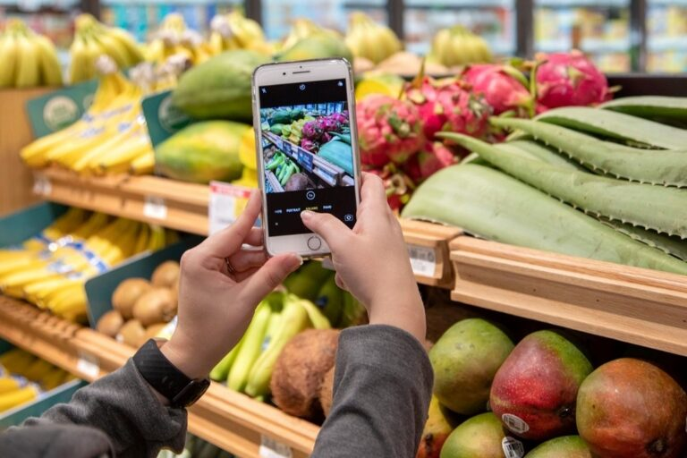 Customer takes picture of fresh fruit at grocery store